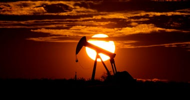 FILE - In this Wednesday, April 8, 2020, file photo, the sun sets behind an idle pump jack near Karnes City, Texas. (AP Photo/Eric Gay, File)