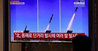People watch a TV screen airing reports about North Korea's firing missiles with file images of missiles at the Seoul Railway Station in Seoul, South Korea, Tuesday, April 14, 2020. (AP Photo/Lee Jin-man)