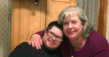 In this April 6, 2018 photo provided by Sharon Reitz, Carolyn Martins-Reitz hugs her son, Thomas Martins, during his birthday celebration in Kearny, N.J. For almost 30 years, a mother and son were inseparable. (Sharon Reitz via AP)