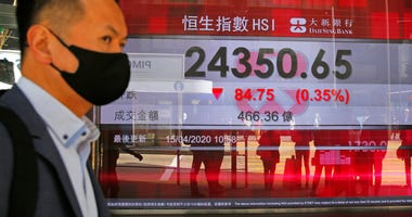 A masked man walks past an electronic board showing Hong Kong share index outside a local bank in Hong Kong, Wednesday, April 15, 2020. (AP Photo/Kin Cheung)