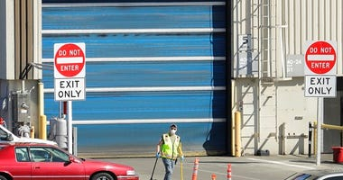 FILE - In this April 13, 2020 file photo, a worker wears a mask as he cleans up an area outside an entrance at Boeing Co.'s airplane assembly facility in Everett, Wash., north of Seattle. (AP Photo/Ted S. Warren, File)