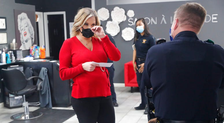 Salon owner Shelley Luther holds a citation and speaks with a Dallas police officer after she was cited for reopening her Salon A la Mode in Dallas, Friday, April 24, 2020.