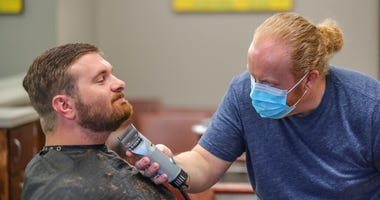 Barber and owner of Chris Edwards wears a mask and cuts the hair of customer David Boswell at Peachtree Battle Barber Shop in Atlanta on Friday, April 24, 2020. (John Spink/Atlanta Journal-Constitution via AP)