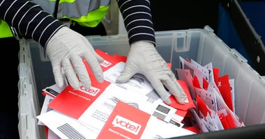 FILE - In this March 10, 2020, file photo wearing gloves, a King County Election worker collect ballots from a drop box in the Washington State primary in Seattle. (AP Photo/John Froschauer, File)