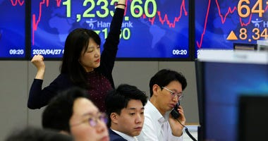 A currency trader stretches at the foreign exchange dealing room of the KEB Hana Bank headquarters in Seoul, South Korea, Monday, April 27, 2020.  (AP Photo/Ahn Young-joon)