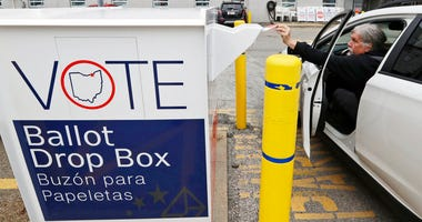 In this April 22, 2020, photo, Jim O'Bryan drops his election ballot in the drop box at the Cuyahoga County Board of Elections in Cleveland.