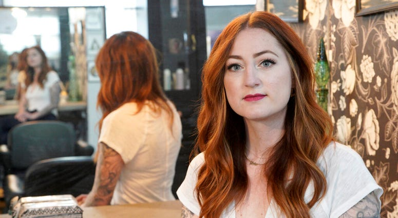 Hairstylist Lacey Ward poses for a photo at the Grey House Salon she co-owns, in Omaha, Neb., Thursday, April 30, 2020. (AP Photo/Nati Harnik)