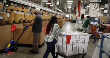 Postal workers wear masks and gloves during the coronavirus pandemic as they physically distance from each other at the United States Postal Service processing and distribution center on Thursday, April 30, 2020, in Oakland, Calif.