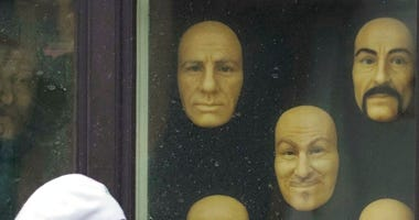 A woman wearing a face mask to protect against coronavirus walks past wax faces displayed in a window of a wax museum in St.Petersburg, Russia, Monday, May 4, 2020.