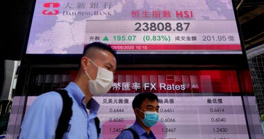 People wearing face masks walk past a bank electronic board showing the Hong Kong share index Tuesday, May 5, 2020.