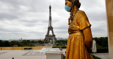 FILE- In this file photo dated Monday, May 4, 2020, a statue wears a mask along Trocadero square close to the Eiffel Tower in Paris.