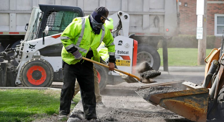 FILE - In this May 6, 2020 file photo, Jarrett Barth, who works for Dagg's Asphalt & Sealcoating, shovels gravel into a backhoe bucket in Lyndhurst, Ohio.