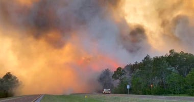 In this image made from video taken May 6, 2020 by the Florida Department of Agriculture and Consumer Services, fire and smoke rise from trees alongside a road in Santa Rosa County, Florida.
