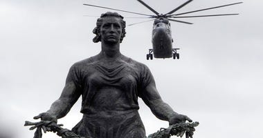 A Mi-26 military helicopter flies over a statue of the Mother Motherland at the Piskaryovskoye Memorial Cemetery where more than half million Leningrad Siege victims were buried during the World War II, during a rehearsal for the Victory Day military air