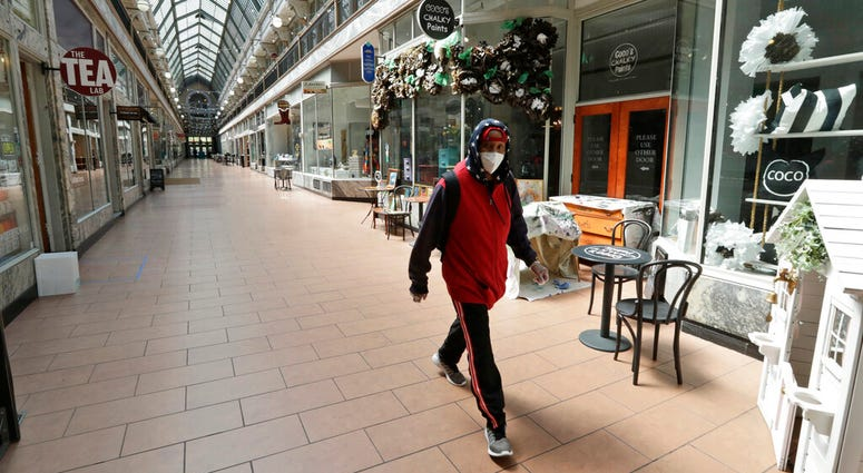 A man walks through the 5th Street Arcade, a selection of indoor shops closed during the pandemic, Thursday, May 7, 2020, in Cleveland.