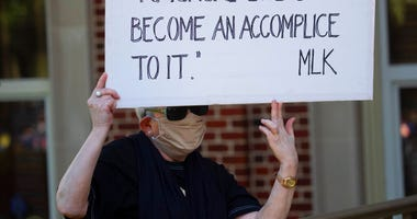 A person holds a sign while watching a rally to protest the shooting of Ahmaud Arbery, Friday, May 8, 2020, in Brunswick Ga. Two men have been charged with murder in the February shooting death of Arbery, a black man in his mid-20s, whom they had pursued