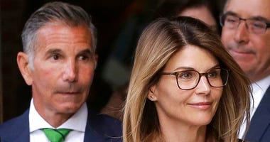 FILE - In this April 3, 2019, file photo, actress Lori Loughlin, front, and her husband, clothing designer Mossimo Giannulli, left, depart federal court in Boston after a hearing in a nationwide college admissions bribery scandal.