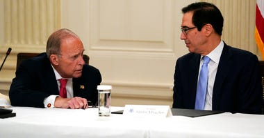 FILE - In this May 8, 2020, file photo Treasury Secretary Steven Mnuchin, right, talks with White House chief economic adviser Larry Kudlow prior to a meeting between President Donald Trump and Republican lawmakers in the State Dining Room of the White Ho