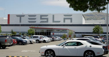 Vehicles are seen parked at the Tesla car plant Monday, May 11, 2020, in Fremont, Calif.