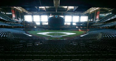 FILE - In this Tuesday, April 28, 2020, file photo, a darkened Chase Field, home of the Arizona Diamondbacks of baseball's National League, sits empty.