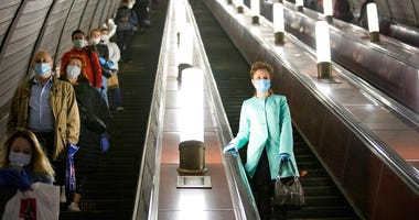 People wearing face masks and gloves to protect against coronavirus, observe social distancing guidelines as they go down the subway on the escalator in Moscow, Russia, Tuesday, May 12, 2020.