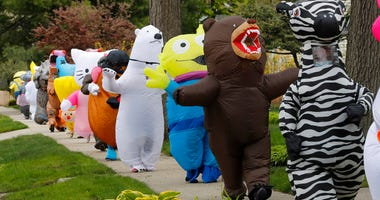 In this Monday, May 11, 2020 photo, members of the T-Rex Walking Club walk through a neighborhood in Ferndale, Mich. While the club members get a kick out of their strolls through town, the idea is to bring a little bit of cheer to their fellow residents