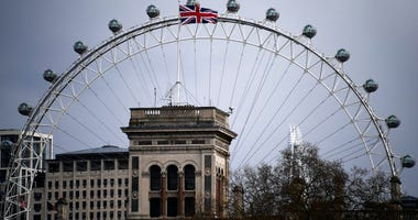 FILE - In this Sunday, March 29, 2020 file photo, the Union Flag waves on the top of Foreign Office, against the backdrop of a closed and empty London Eye, due to the Coronavirus outbreak, in London.