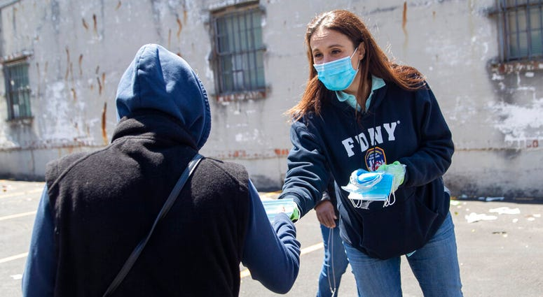 Democratic New York 14th Congressional District candidate Michelle Caruso-Cabrera, right, distributes masks at the St. Mark AME Church – The Voices of Hagar food pantry during the coronavirus pandemic, Tuesday, May 12, 2020, in the Flushing neighborhood o