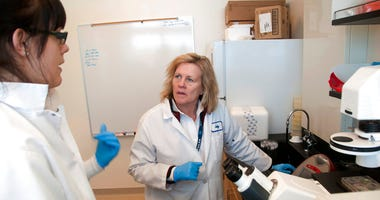 FILE - In this Feb. 28, 2011, file photo, Director of research Judy Mikovits talks to a graduate student and research associate in the lab, at the Whittemore Peterson Institute for Neuro-Immune Disease, in Reno, Nev. T