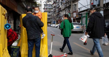 In this photo taken Wednesday, April 1, 2020, residents walk past a sealed off neighborhood in Wuhan, central China's Hubei province.