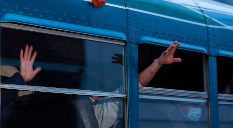 In this May 4, 2020, file photo, Guatemalans deported from the U.S., wave from a bus after arriving at La Aurora airport in Guatemala City. (AP Photo/Moises Castillo, File)