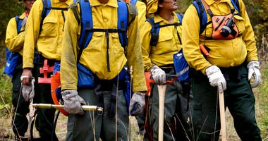 ILE - IN this Aug. 18, 2017, file photo, exhaustion reads on the face of a firefighter from Noorvik, Alaska, while he and his team watch for spot fires that threaten to jump the line on the Lolo Peak fire, in Missoula, Mont.