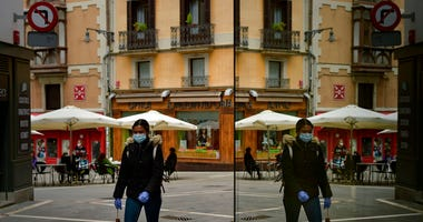 A woman wearing a face mask to protect against coronavirus is reflected in a gwindow while passing along a street next to some bar terraces, in Pamplona, northern Spain, Wednesday, May 13, 2020.