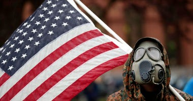 A protester wears a gas mask and carries an American flag during a rally in response to Michigan's coronavirus stay-at-home order at the State Capitol in Lansing, Mich., Thursday, May 14, 2020.