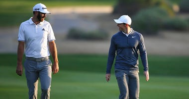 FILE - In this Jan. 18, 2018, file photo, Dustin Johnson of the United States, left, and Rory McIlroy of Northern Ireland talk on the 10th fairway during the first round of the Abu Dhabi Championship golf tournament in Abu Dhabi, United Arab Emirates.