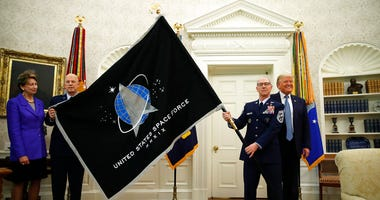 President Donald Trump stands as Chief of Space Operations at US Space Force Gen. John Raymond, second from left, and Chief Master Sgt. Roger Towberman, second from right, hold the United States Space Force flag as it is presented in the Oval Office of th