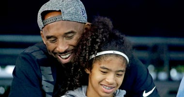 FILE - In this July 26, 2018, file photo, former Los Angeles Laker Kobe Bryant and his daughter Gianna watch during the U.S. national championships swimming meet in Irvine, Calif.