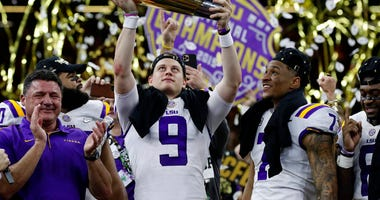 FILE - In this Monday, Jan. 13, 2020, file photo, LSU quarterback Joe Burrow holds the trophy as safety Grant Delpit looks on after LSU defeated Clemson 42-25 in the NCAA College Football Playoff national championship game.  (AP Photo/Sue Ogrocki, File)