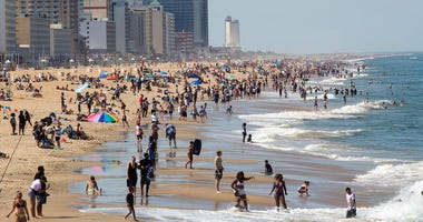 Warm weather draws crowds to the oceanfront, Saturday, May 16, 2020 in Virginia Beach, Va. (Kaitlin McKeown/The Daily Press via AP)