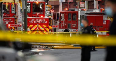 os Angeles Police Department officers work the scene of a structure fire that injured multiple firefighters, according to a fire department spokesman, Saturday, May 16, 2020, in Los Angeles.