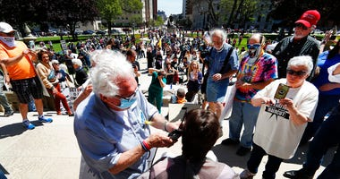 Barber Karl Manke, of Owosso, gives a free haircut on the steps of the State Capitol during a rally in Lansing, Mich., Wednesday, May 20, 2020.