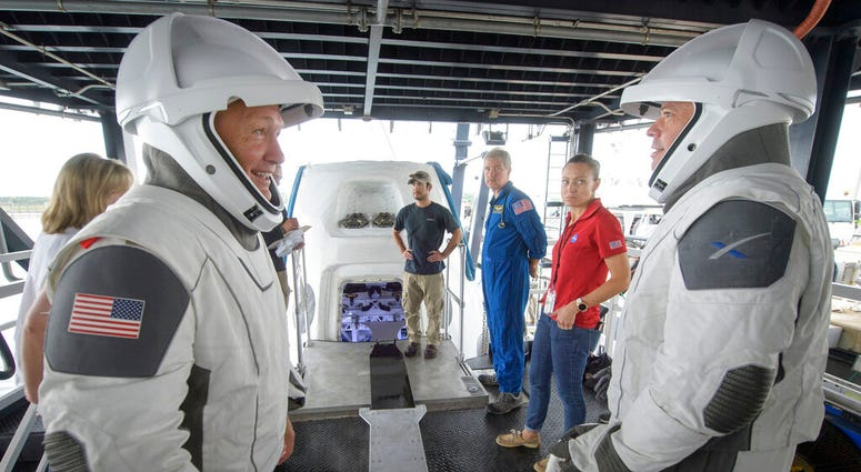 FILE - In this Aug. 13, 2019 file photo, NASA astronauts Doug Hurley, left, and Bob Behnken work with teams from NASA and SpaceX to rehearse crew extraction from SpaceX's Crew Dragon, which will be used to carry humans to the International Space Station,