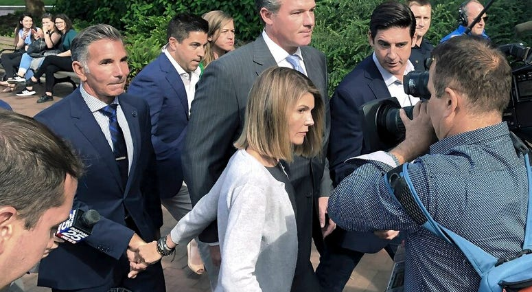 In this Aug. 27, 2019, file photo, Lori Loughlin departs federal court with her husband, clothing designer Mossimo Giannulli, left, in Boston, after a hearing in a nationwide college admissions bribery scandal. (AP Photo/Philip Marcelo, File)