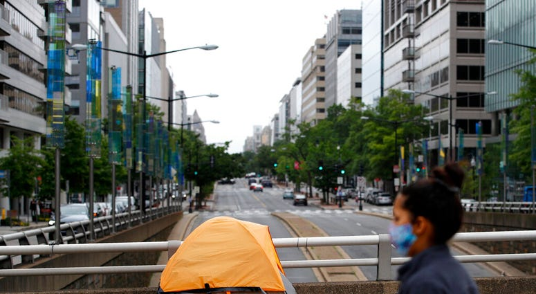 A homeless person's tent sits above a quiet K Street Northwest as a woman wearing a face mask to protect against the spread of the new coronavirus walks past, Thursday, May 21, 2020, in Washington.