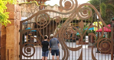 FILE - In this Thursday, May 14, 2020, file photo, guests peer through the closed gate to Universal's Islands of Adventure beside Universal CityWalk, in Orlando, Fla. (Stephen M. Dowell/Orlando Sentinel via AP, File)