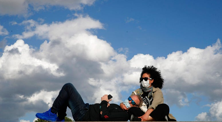 Parisians, wearing protective masks, sit in the sun along the closed Tuileries garden in Paris, Saturday, May 23, 2020 as France gradually lifts its COVID-19 lockdown.