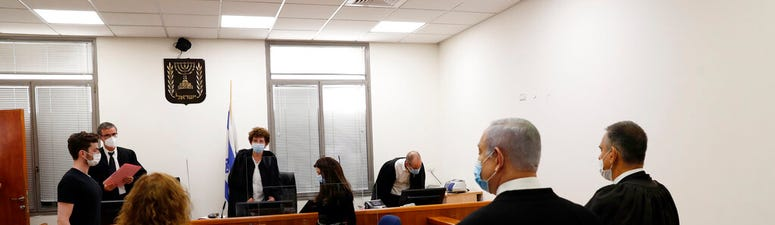 sraeli Prime Minister Benjamin Netanyahu, second right, stands while the judges enter the court room as his corruption trial opens at the Jerusalem District Court, Sunday, May 24, 2020.