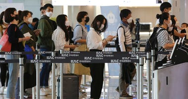 Passengers wearing face masks line up to board their planes at the domestic flight terminal of Gimpo airport in Seoul, South Korea, Wednesday, May 27, 2020.