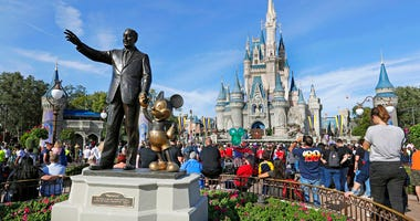 FILE - In this Jan. 9, 2019 photo, guests watch a show near a statue of Walt Disney and Micky Mouse in front of the Cinderella Castle at the Magic Kingdom at Walt Disney World in Lake Buena Vista, part of the Orlando area in Fla.