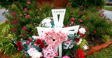 In this May 22, 2020, photo, a group of flowers and a cross mark the entrance to Jason Nixon's neighborhood in Virginia Beach, Va. The flowers are a memorial to Kate Nixon who was killed in last year's shootings at a Virginia Beach municipal building.